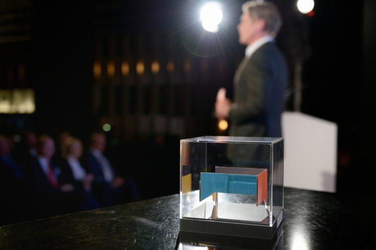 Moderator Hajo Schumacher & Gewinnertrophäe